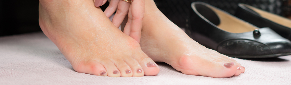 Woman holding her foot from pain caused by bunions.